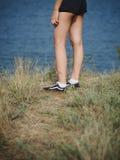 女孩在小山的` s腿特写镜头  站立在被弄脏的自然本底的妇女 有效的生活方式概念 复制空间 免版税库存照片