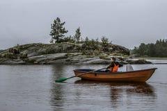 女孩在小船单独航行在湖中间 免版税图库摄影