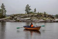 女孩在小船单独航行在湖中间 图库摄影