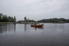 女孩在小船单独航行在湖中间 库存图片