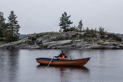 女孩在小船单独航行在湖中间 免版税库存照片