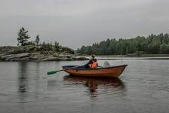 女孩在小船单独航行在湖中间 库存照片