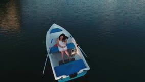 女孩在小船坐并且改正头发 影视素材