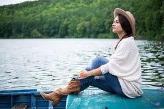 女孩在小船坐湖 免版税库存图片