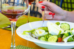 女孩在小酒馆拿着一把叉子并且吃希腊沙拉用红葡萄酒 库存图片