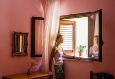 女孩在屋子里在乡间别墅窗口里 库存图片