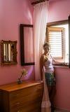 女孩在屋子里在乡间别墅窗口里 图库摄影