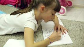 女孩在屋子里画在说谎在地板上的册页的标志 影视素材