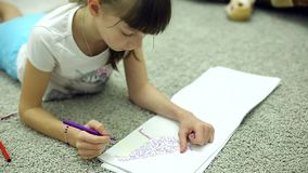 女孩在屋子里画在说谎在地板上的册页的标志 股票录像
