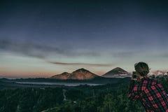 女孩在山火山Batur的电话做一张照片在背景夜空的与星 库存照片