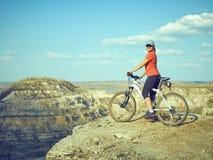 女孩在山的一辆自行车 库存图片