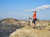 女孩在山的一辆自行车 免版税库存照片