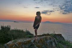 女孩在岩石和神色站立在海和日落的美丽的景色 免版税图库摄影