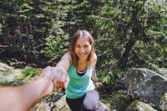 女孩在岩石,伙伴上升拔出协助的手 免版税图库摄影
