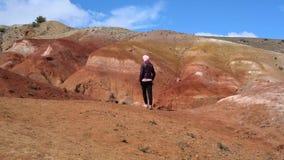 女孩在峡谷的背景跨步和五颜六色的小山然后中止 影视素材