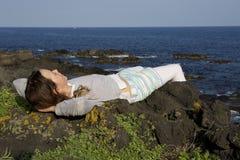 女孩在峭壁岩石放松 免版税库存照片