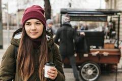 女孩在布拉格喝从一个一次性杯子的咖啡在街道上 库存照片