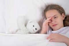 女孩在床上去睡,在一个白色玩具熊旁边 库存照片