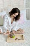 女孩在床上坐倾吐咖啡罐 库存图片