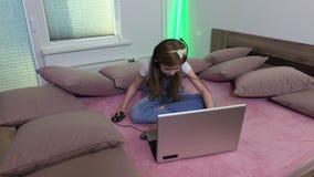 女孩在床上坐并且使用膝上型计算机 影视素材