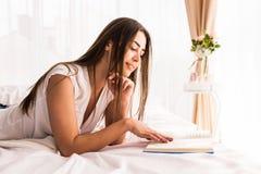 女孩在床上的阅读书在家 免版税库存图片