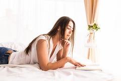 女孩在床上的阅读书在家 库存图片