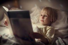 女孩在床上读一本书 免版税图库摄影