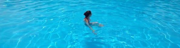 女孩在度假在旅馆游泳的在水池 免版税库存照片