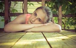 女孩在庭院里,眺望台的,坐大阳台在夏天 库存图片