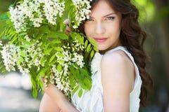 女孩在开花的庭院里 库存照片