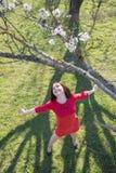 女孩在开花的扁桃下 免版税库存图片