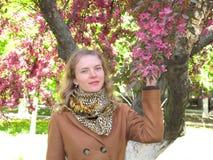 女孩在开花的树附近的公园 免版税库存图片