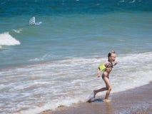 女孩在恐惧跑从汹涌的海 库存图片