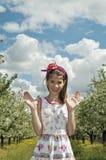 女孩在愉快酸樱桃的果树园 免版税库存图片