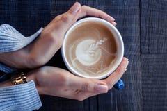 女孩在手上拿着一个蓝色杯子热奶咖啡在一张木桌上 免版税库存照片