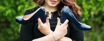 女孩在手上拿着鞋子 库存照片