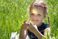 女孩在手上的拿着一枚bitcoin cryptocurrency硬币 与金币的儿童游戏坐草 库存照片