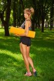 女孩在手上的拿着瑜伽席子站立在公园 库存图片