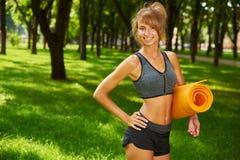 女孩在手上的拿着瑜伽席子站立在公园 免版税库存照片