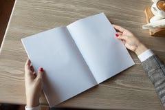 女孩在手中拿着杂志模型A4格式 库存照片