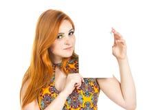 女孩在手中确信地看与纸的照相机 红发 库存照片