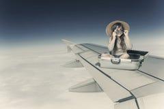 女孩在手提箱坐在飞行中飞机的翼 库存照片