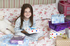 女孩在拿着圣诞节礼物的床上 库存图片
