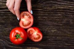 女孩在拿着蕃茄的手上 库存照片