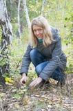 女孩在拿着蘑菇的桦树森林里。 免版税库存图片