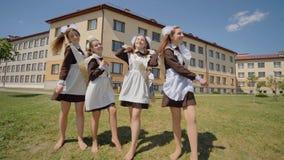 女孩在挥动的校服毕业摆在和 俄国毕业生庆祝最后教学日 影视素材
