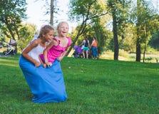 女孩在接力赛竞争 跳跃在袋子 他们笑并且跌倒 库存照片