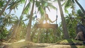 女孩在摇摆和神色摇摆在热带海滨的日落 自由,休息,假期,旅行概念 股票视频