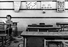 女孩在教室在一个小村庄, Sapa,越南里面的阅读书 库存图片