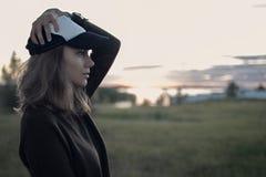 女孩在日落的外形和领域画象帽子的与tal的 免版税库存照片